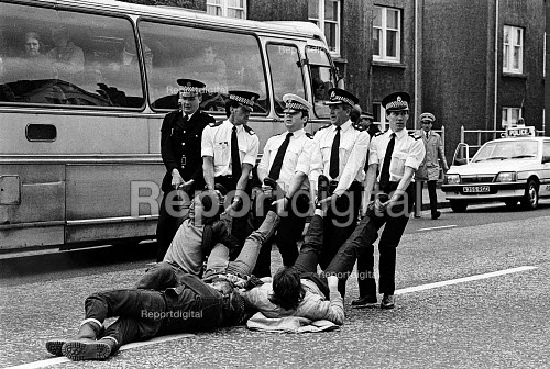 Miners Strike, polices stop coaches of miners traveling to picket coal leaving British Steels Hunterston Terminal. The 300 miners then sat down in the road and were dragged away by police and arrested. Scotland. - John Sturrock - 1984-05-10