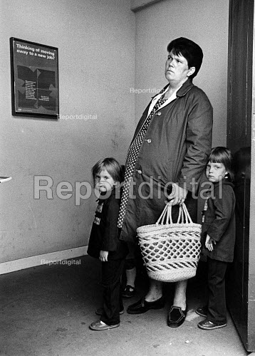 A mother with her two children, outside of the DHSS Office in Brixton, London - John Sturrock - 1978-04-20