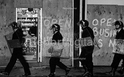 Police occupy Grimethorpe pit village, walking past a shop with boarded up windows, Yorkshire, Miners strike. - John Sturrock - 1984-10-16