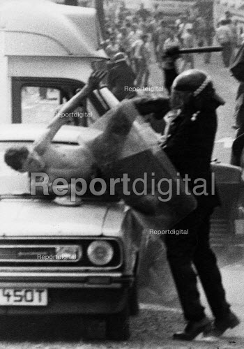 Senior police officer attacking a miner guarding his car. The attempt to prosecute the miner for riot collapsed. Orgreave coke works Miners strike Sheffield South Yorkshire - John Harris - 1984-06-18
