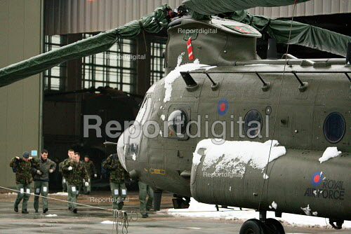 RAF personell walking out of a hanger in the snow past a Chinook helicopter at RAF in Hampshire. - Justin Tallis - 2010-01-13