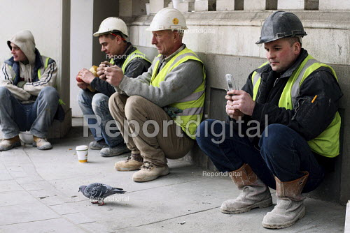Construction workers on their lunch break sitting down together and having a chat. London. - Justin Tallis - 2010-02-03