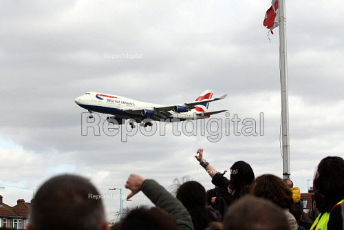 Thumbs down and booing a British Airways plane overhead. British Airways cabin crew on the third day of strike action over pay and working conditions. London Heathrow Airport. - Justin Tallis - 2010-03-22