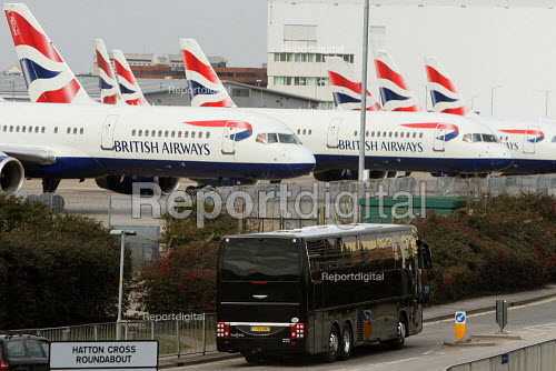 A coach with blacked out windows carrying scab workers past rows of grounded planes. British Airways cabin crew on the third day of strike action over pay and working conditions. London Heathrow Airport. - Justin Tallis - 2010-03-22