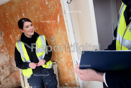 Apprentice working for her NVQ level 2 in plumbing, being asked questions assessing her progress by a supervisor whilst installing a bath in a bathroom. Nottingham City Homes, One In A Million Scheme. Nottingham. - Justin Tallis - 2010-03-17