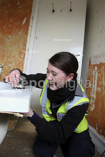 Apprentice working for her NVQ level 2 in plumbing, installing a bath in a bathroom. Nottingham City Homes, One In A Million Scheme. Nottingham. - Justin Tallis - 2010-03-17