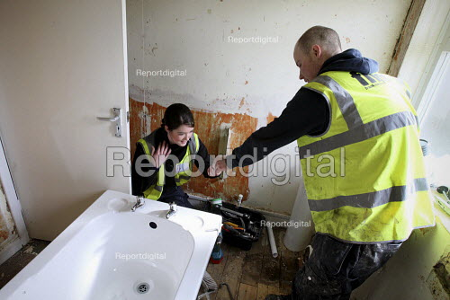 Apprentice working for her NVQ level 2 in plumbing, being helped to install a bath in a bathroom. Nottingham City Homes, One In A Million Scheme. Nottingham. - Justin Tallis - 2010-03-17