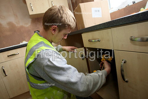 Apprentice working towards his NVQ level 2 in carpentry and joinery. Installing a kitchen unit whilst working for the Nottingham City Homes, One In A Million Scheme. - Justin Tallis - 2010-03-17