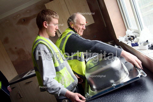 Apprentice working towards his NVQ level 2 in carpentry and joinery. Being helped to install a kitchen sink by an older worker whilst working for the Nottingham City Homes, One In A Million Scheme. - Justin Tallis - 2010-03-17