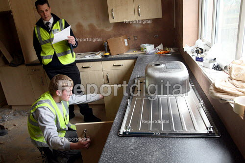 Apprentice working towards his NVQ level 2 in carpentry and joinery. Installing a kitchen unit and being watched by a supervisor whilst working for the Nottingham City Homes, One In A Million Scheme. - Justin Tallis - 2010-03-17