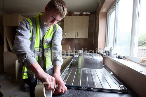 Apprentice working towards his NVQ level 2 in carpentry and joinery. Installing a kitchen sink whilst working for the Nottingham City Homes, One In A Million Scheme. - Justin Tallis - 2010-03-17