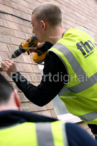 Apprentice electrician installing wall fan whilst working towards his 2330 City and Guilds Electrotechncial Technology certificate. Nottingham City Homes, One In A Million Scheme. Nottingham. - Justin Tallis - 2010-03-17
