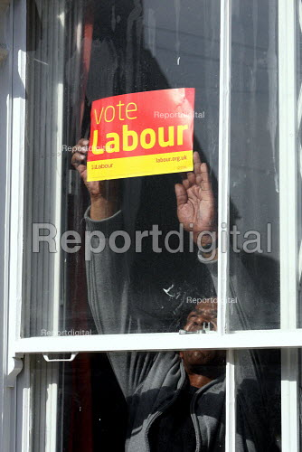 A Labour Party supporter putting up a poster in his window. Tooting South London. - Justin Tallis - 2010-04-21