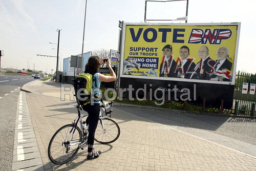 A cyclist stops to take a photograph of a defaced British National Party bring our troops home billboard by the side of the road in Barking. East London. - Justin Tallis - 2010-04-24