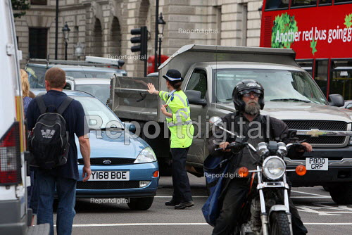 Police Community Support Officer directing heavily congested traffic during rush hour. London. - Justin Tallis - 2010-07-02
