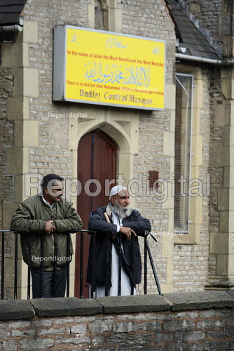 Muslims outside the mosque as English Defence League protestors are kept away by riot police and local people. Dudley. - Justin Tallis - 2010-07-17
