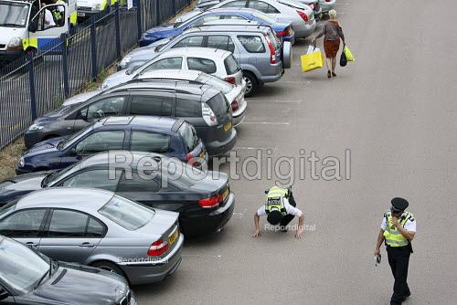 British Transport Police checking underneath cars in a large car park in Luton. - Justin Tallis - 2010-07-22