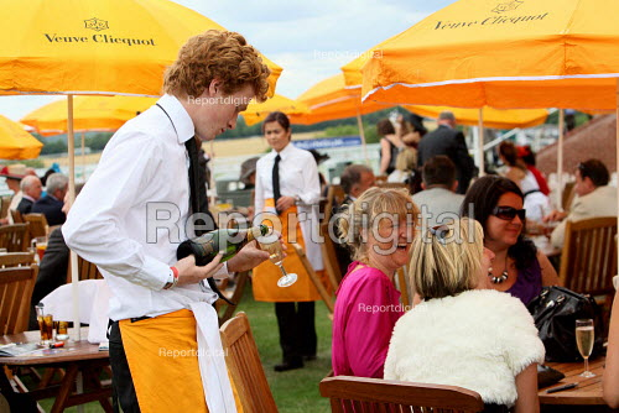 Waiter serving racegoers at Venue Cliquot champagne bar. Goodwood racecourse. - Justin Tallis - 2010-07-29