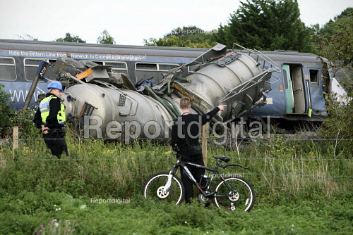 Policeman speaking to a local boy at the wreckage of the train and a waste disposal tanker which collided at an unmanned level crossing. Little Cornard. Suffolk. - Justin Tallis - 2010-08-18