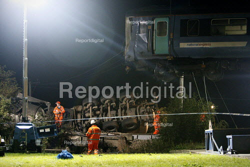 Recovery workers use a huge crane to lift a damaged train carriage from the tracks. The wreckage of the train and a waste disposal tanker which collided at an unmanned level crossing. Little Cornard. Suffolk. - Justin Tallis - 2010-08-19