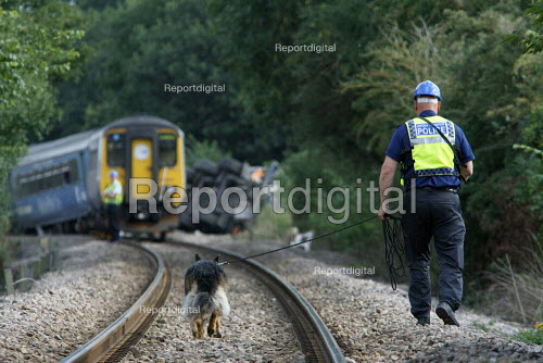 Police officer and sniffer dog checking for passengers along the track at the wreckage of the train and a waste disposal tanker which collided at an unmanned level crossing. Little Cornard. Suffolk. - Justin Tallis - 2010-08-18