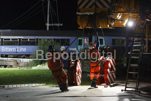 Recovery workers getting their winch ready in preparation to lift the wreckage of a train from the tracks. The train and a waste disposal tanker collided at an unmanned level crossing. Little Cornard. Suffolk. - Justin Tallis - 2010-08-18