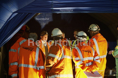 Recovery workers at a management meeting before lifting a trian from the tracks. The train and a waste disposal tanker collided at an unmanned level crossing. Little Cornard. Suffolk. - Justin Tallis - 2010-08-18