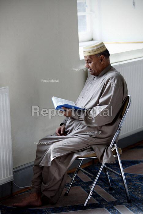 A man reading the Koran during friday prayers at Brick Lane Mosque, East London. - Justin Tallis - 2010-09-03