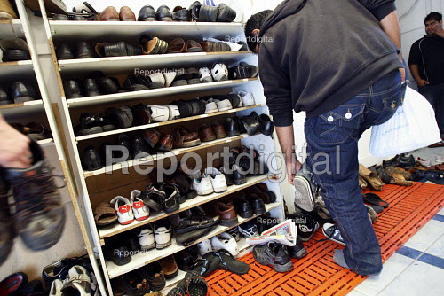 Man taking off his shoes for friday prayers at Brick Lane Mosque, East London. - Justin Tallis - 2010-09-03