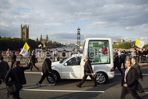 Pope Benedict XVI, flanked by his security team, is greeted by a small group of supporters whilst crossing Lambeth Bridge in the popemobile. London. - Justin Tallis - 2010-09-17