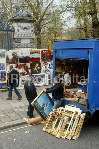 Souvenir art dealer having in discussion next to his van. Piccadilly, Central London. - Justin Tallis - 2010-11-20