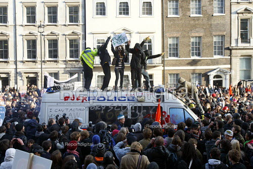 Students vandalise a riot van the police left unattended in the middle of Whithall. Student Walkout Against Fees. Protest against education cuts and increased tuition fees, Whitehall, London. - Justin Tallis - 2010-11-24