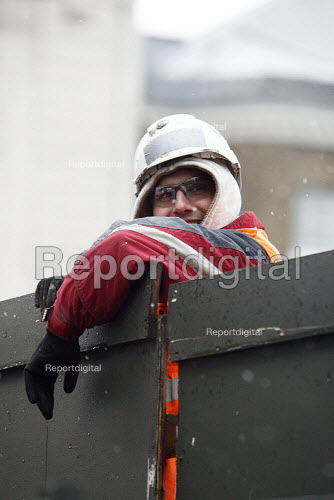 A workman leaning over a temporary wall in the snow. London. - Justin Tallis - 2010-11-30
