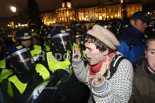 A student holding his hands up as riot police force him back. Students walk out in protest against plans to raise tuition fees and cuts in university funding. Trafalgar Square, London. - Justin Tallis - 2010-11-30