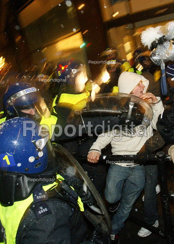 Riot police force students back by hitting them with shields. Students walk out in protest against plans to raise tuition fees and cuts in university funding. Trafalgar Square, London. - Justin Tallis - 2010-11-30