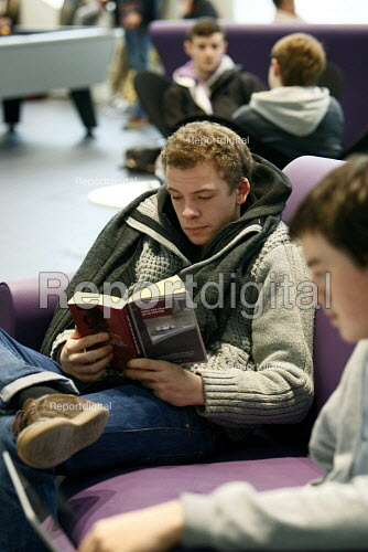 Student trying to read his book during lunch break in The Big Space common room area. Ravensbourne specialist higher education college, Greenwich, London. - Justin Tallis - 2010-12-06