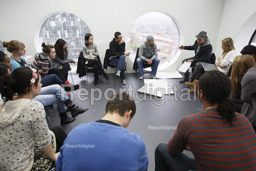 Students studying for a Foundation Diploma in Art and Design having a critique of their work. Held in an open plan teaching area they are showing of their designs to the class. Ravensbourne specialist higher education college, Greenwich, London. - Justin Tallis - 2010-12-06