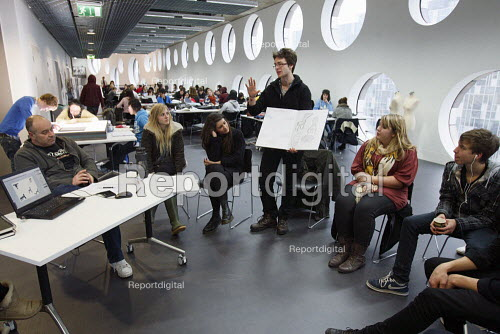 Students studying for a Foundation Diploma in Art and Design having a crit held in an open plan teaching area showing of their designs to the class. Ravensbourne specialist higher education college, Greenwich, London. - Justin Tallis - 2010-12-06