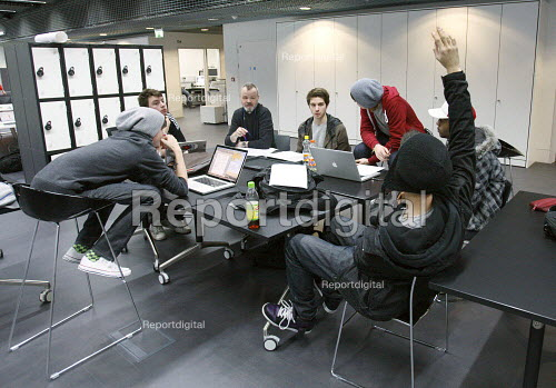 Student with his had up to ask a question in an open plan teaching area at Ravensbourne specialist higher education college, Greenwich, London. - Justin Tallis - 2010-12-06
