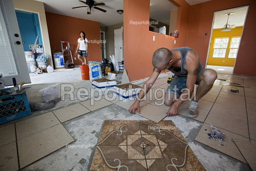 New Orleans, Louisiana - A volunteer with Common Ground Relief lays tile as the organization rebuilds a house for a resident seven years after the city was devastated by Hurricane Katrina. - Jim West - 2012-11-05