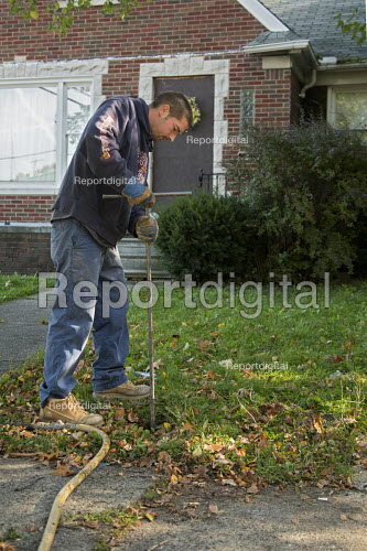 Detroit, Michigan - A worker from the city's contractor, Homrich, shuts off water service to a home in Detroit. As it tries to recover from bankruptcy, the city is shutting off water to tens of thousands of residents living in poverty who are behind on their bills. - Jim West - 2014-10-09