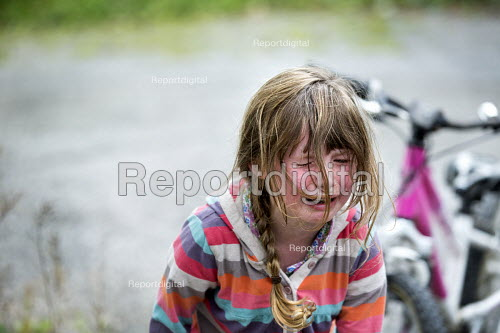 A young girl in tears having fallen off her bike and hurt her leg. Wrexham, North Wales - Paul Box - 2013-09-15