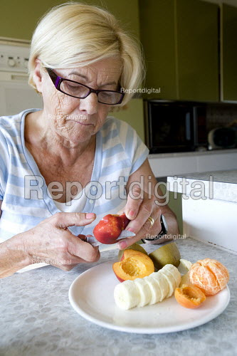 An elderly woman eating fruit for breakfast. - Paul Box - 2009-08-10
