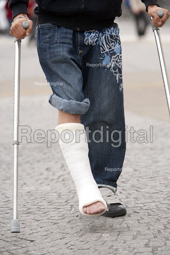 A young man with a broken leg in a plaster cast walks on his crutches. - Paul Box - 2009-09-02