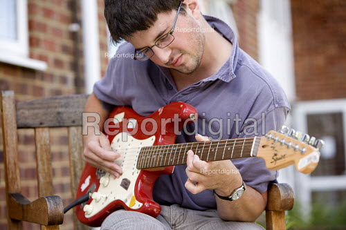 Resident with multiple sclerosis playing his guitar. Selwood manage and maintain quality affordable housing and provide support services for people in housing need - Paul Box - 2009-07-30