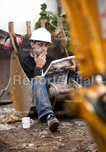 Builder taking a break sitting in a digger bucket and reading the property for sales pages of a local newspaper. - Paul Box - 2008-08-13