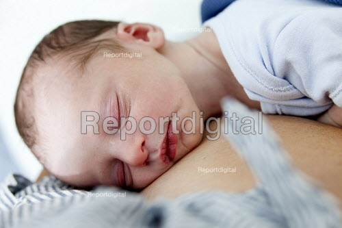 A new born baby sleeps with his mother. The mother is an IVF patient who has obstetric cholestasis a rare complication of pregnancy. Which is a build-up of bile acids in the bloodstream and liver. Southmead hospital, Bristol. - Paul Box - 2012-09-26