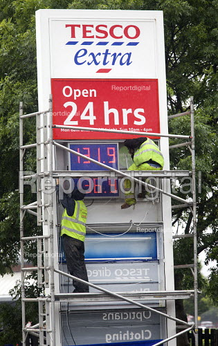 Tesco Extra petrol station. Workers maintaining the price of fuel sign. - Paul Box - 2012-06-11