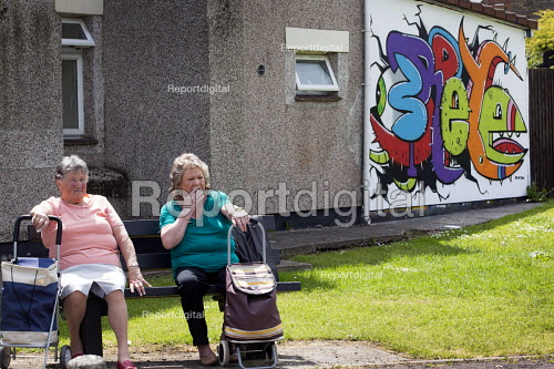Two ladies have a cigarette on a bench in front of graffiti, Southville, Bristol. - Paul Box - 2013-05-31