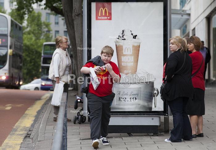 An overweight boy walks past a Mcdonalds advertisement whilst his mother watches him, Bristol - Paul Box - 2013-08-24